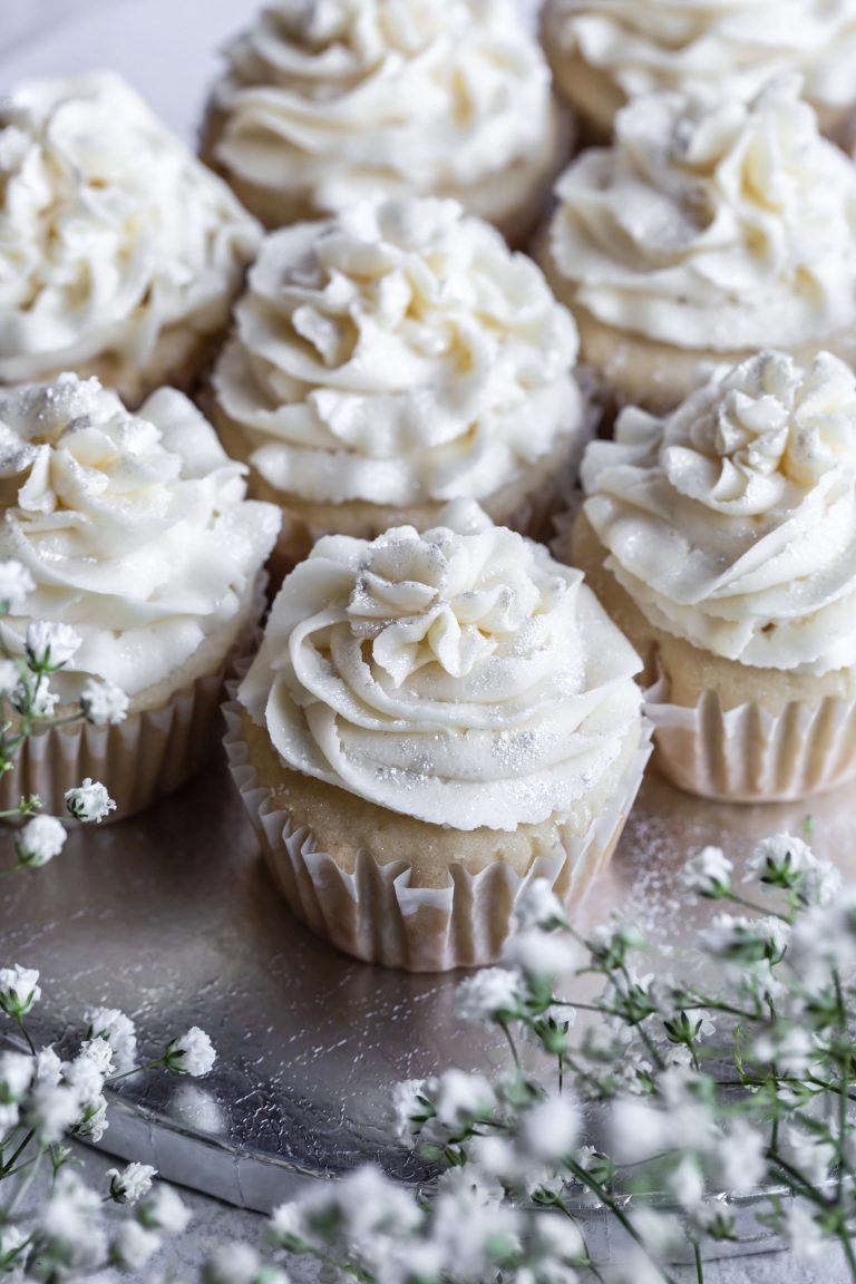 Silver platter of vegan white wedding cupcakes with white frosting.