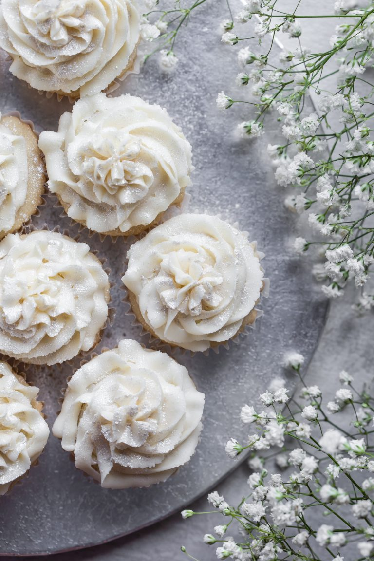 Silver platter of white vegan wedding cupcakes with white flowers on the side.