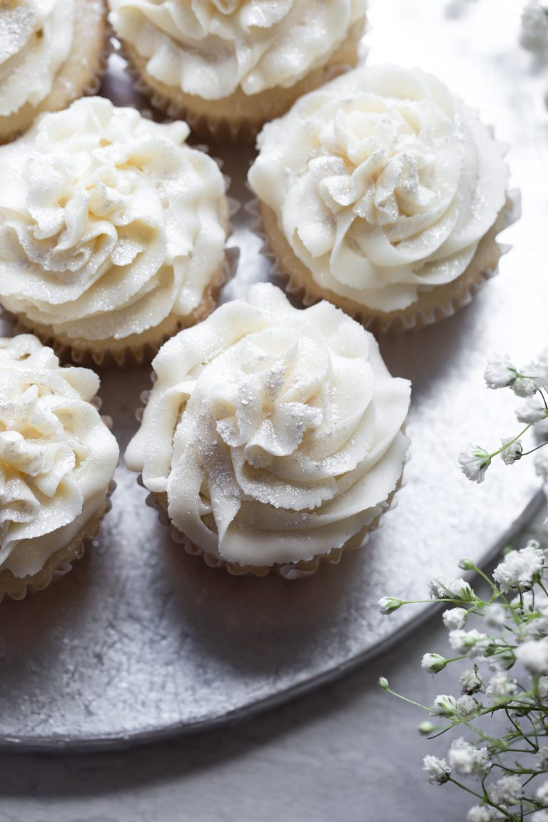 Silver platter of several vegan white wedding cupcakes with white frosting.