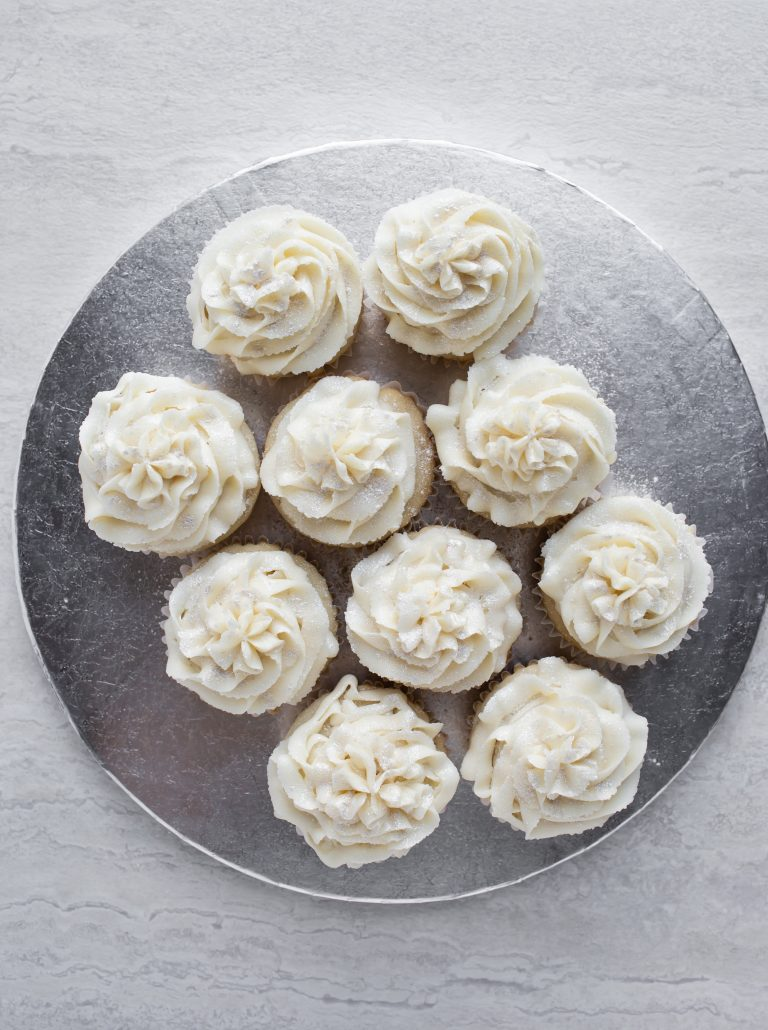 Overhead image of a silver platter of white vegan wedding cupcakes.
