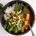 vegan Thai green curry sauce with sweet potatoes in wood bowl
