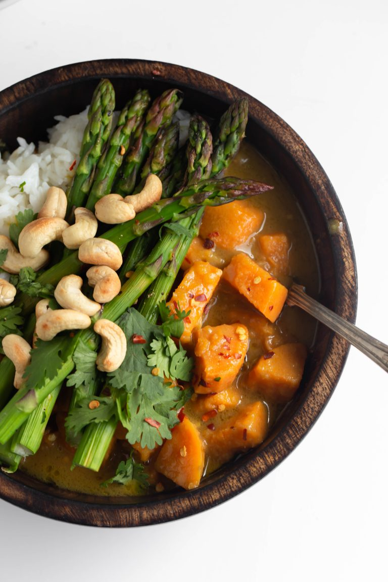 Vegan thai green sweet potato curry topped with asparagus