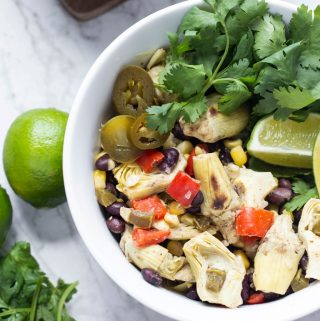 Roasted Artichoke Salad in white bowl with lime