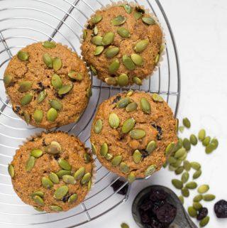 4 vegan pumpkin muffins with pumpkin seeds and cherries