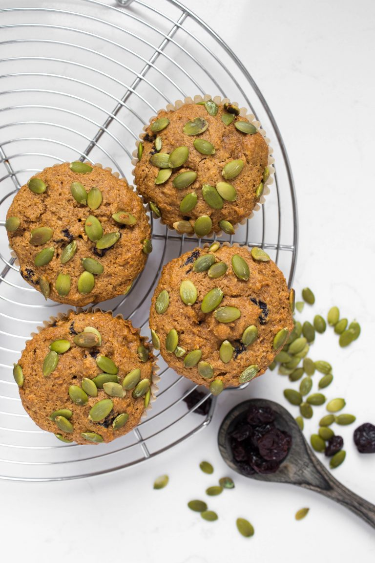4 vegan pumpkin muffins with pumpkin seeds and cherries