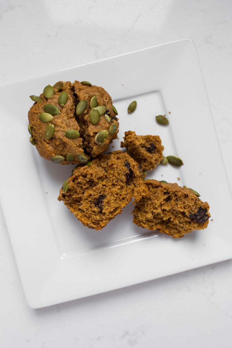 Cut open vegan pumpkin muffin with pumpkin seeds