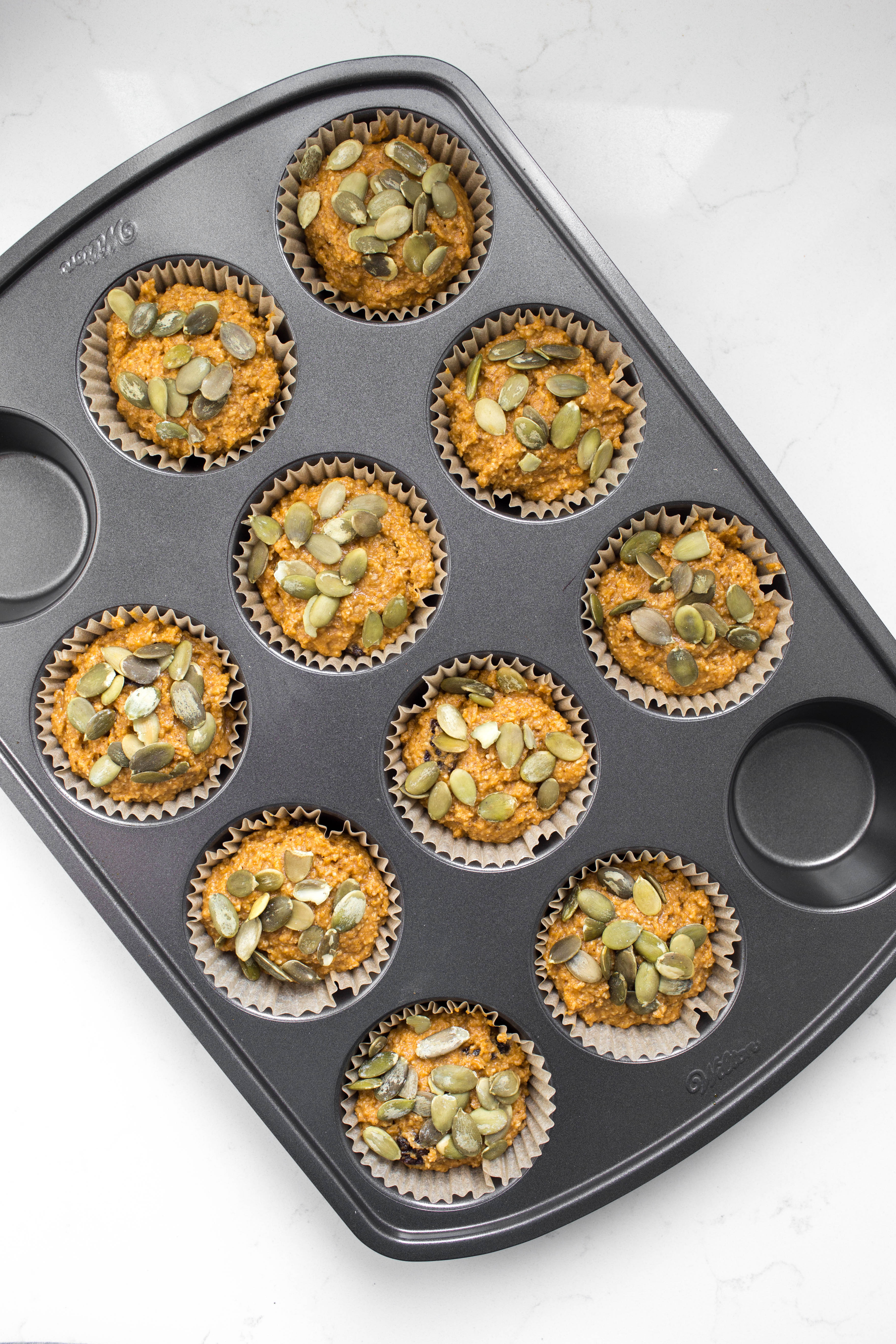 Muffin pan with pre-baked vegan pumpkin batter