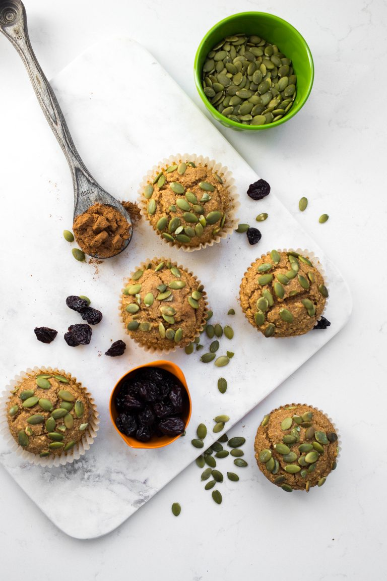 Several vegan pumpkin muffins with pumpkin seeds on top