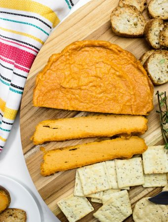 Slices of smoky baked cashew cheese and crackers on platter