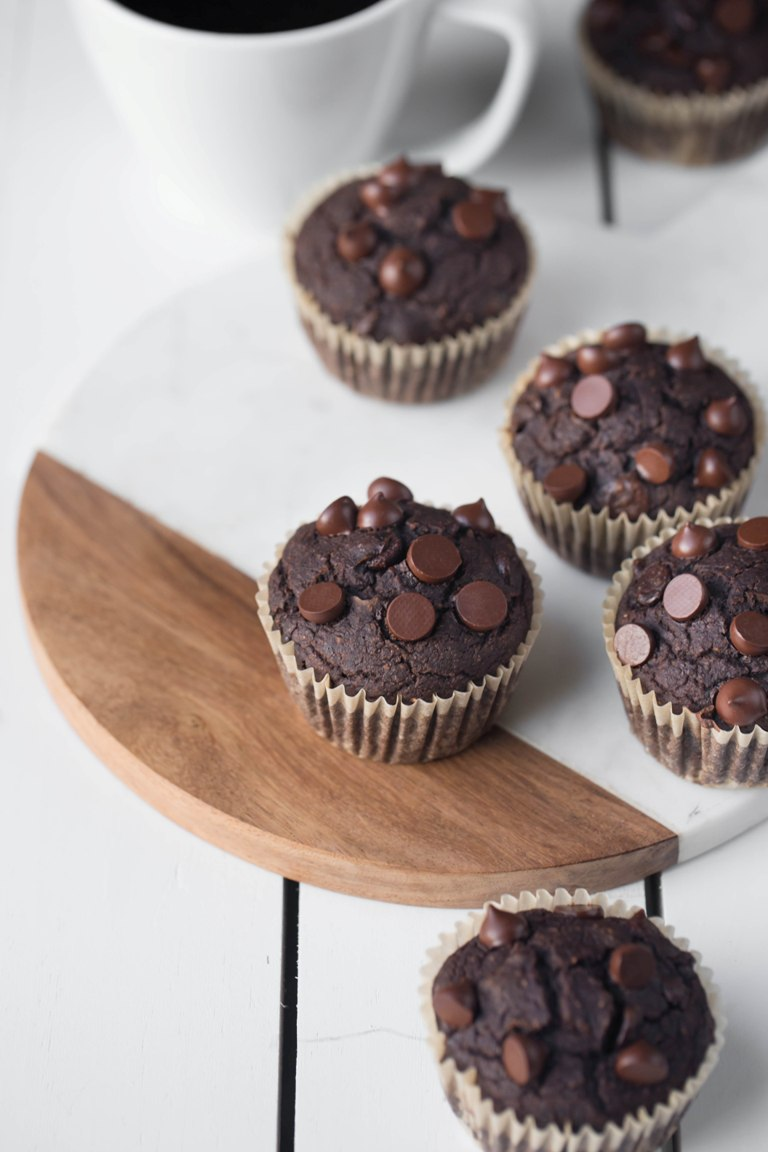 Several vegan chocolate zucchini muffins on white table