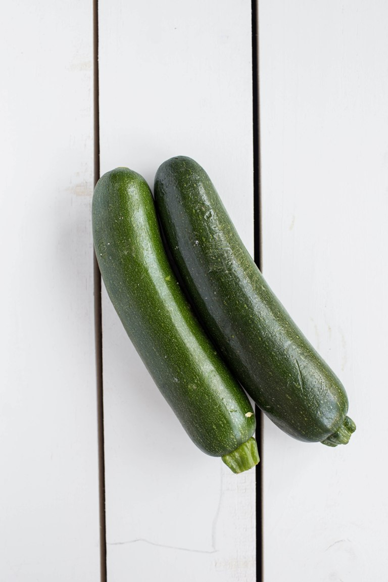 2 zucchini on white table