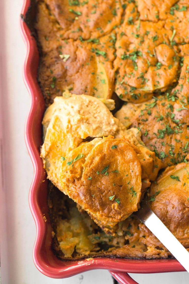 Closeup image of a spoon holding vegan scalloped potatoes.