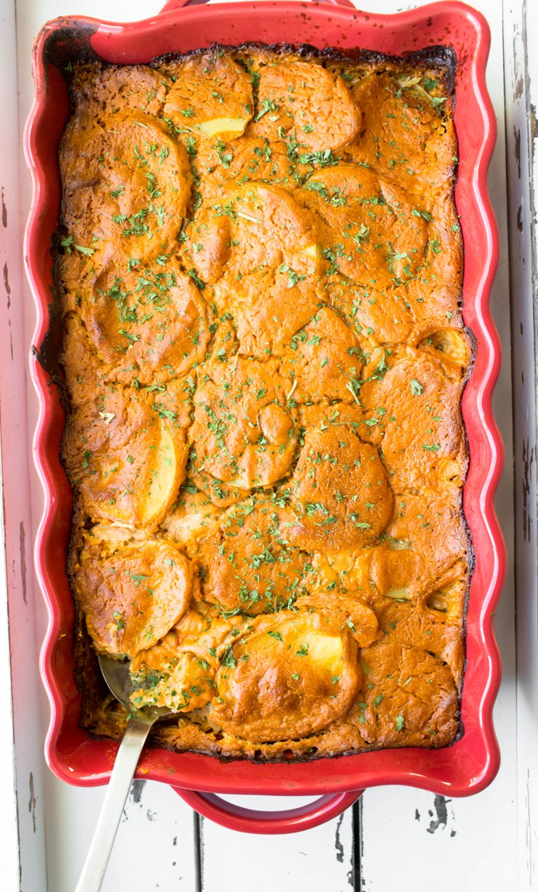 Large red casserole dish of baked vegan scalloped potatoes.