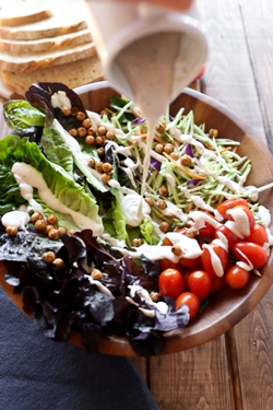 Wooden bowl with a large salad and vegan ranch dressing poured.