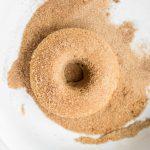 Vegan cinnamon sugar donut in bowl of sugar
