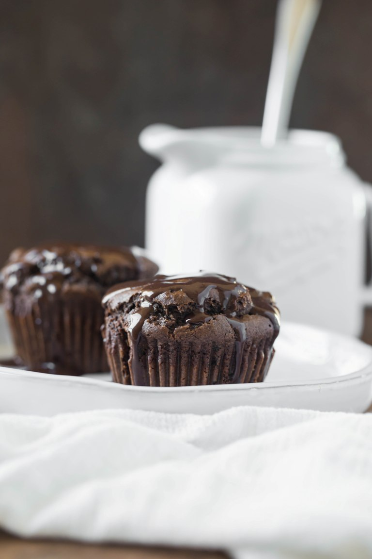 2 chocolate muffins with chocolate sauce on top