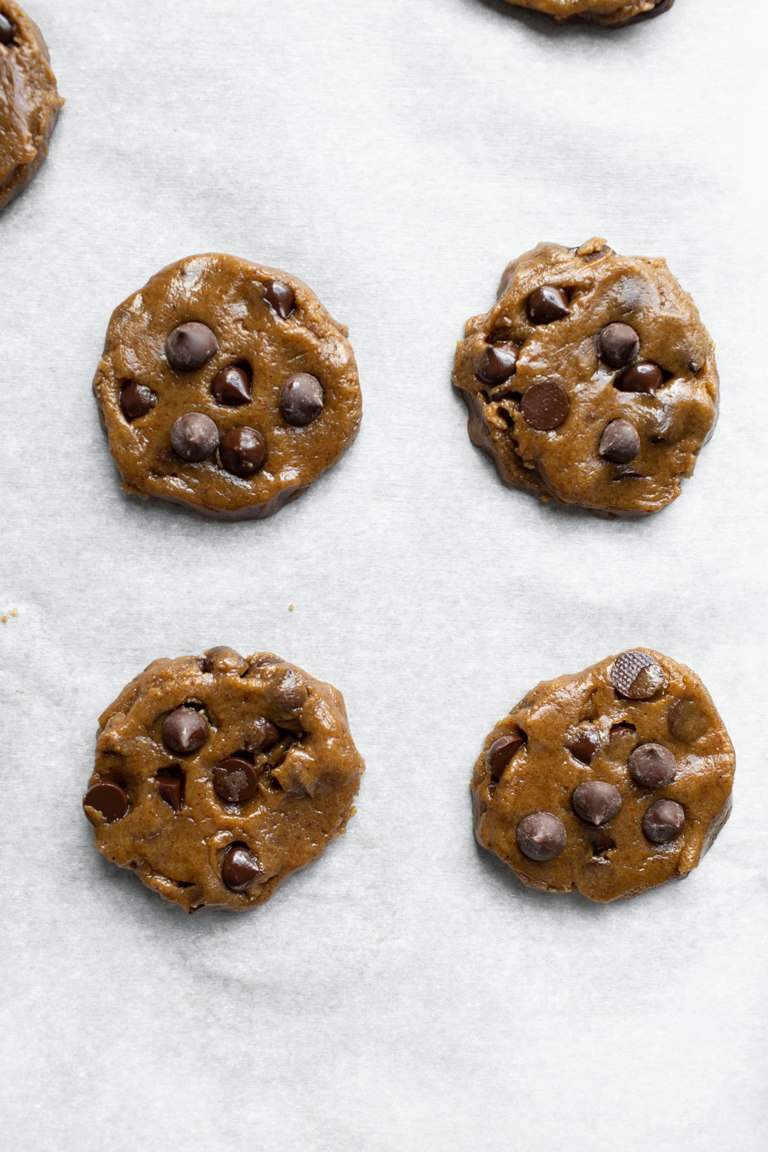 Prebaked chocolate chip cookies on parchment paper