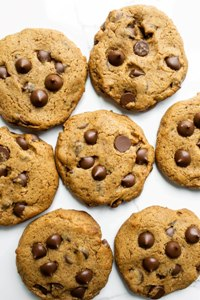 scattered vegan chocolate chip cookies on white board