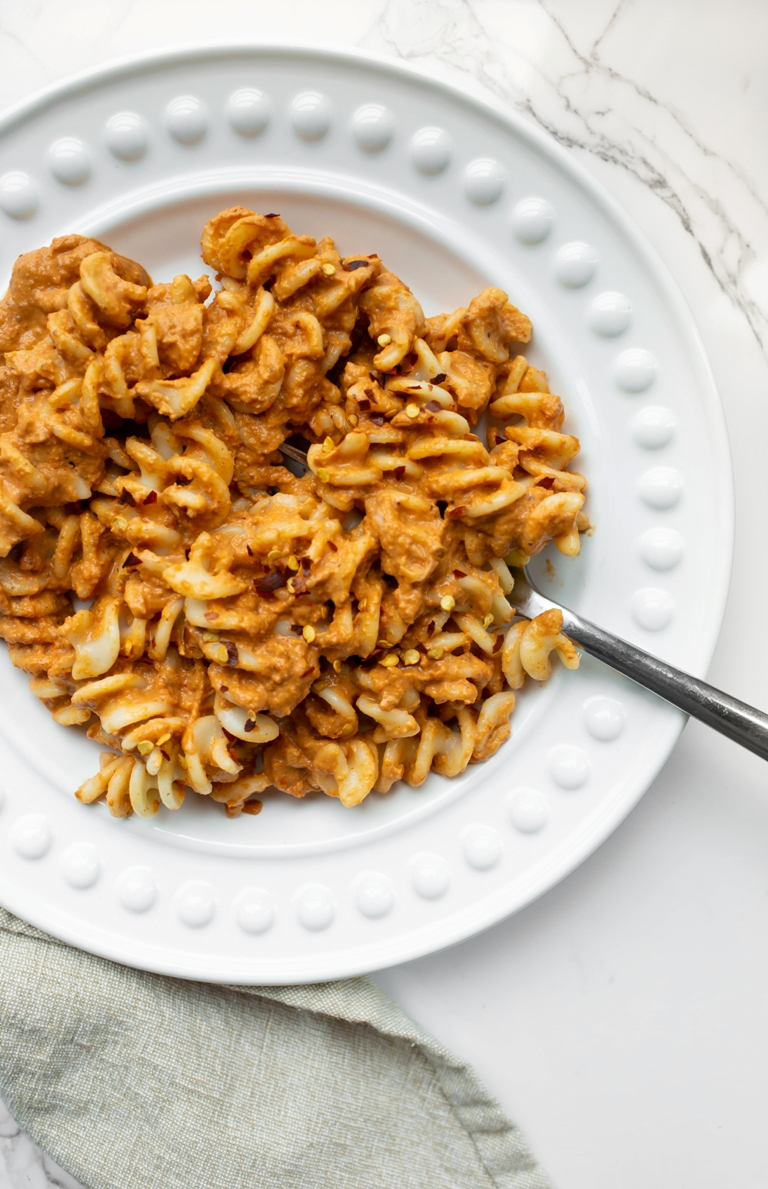 romesco sauce mixed in with fusilli pasta on white plate