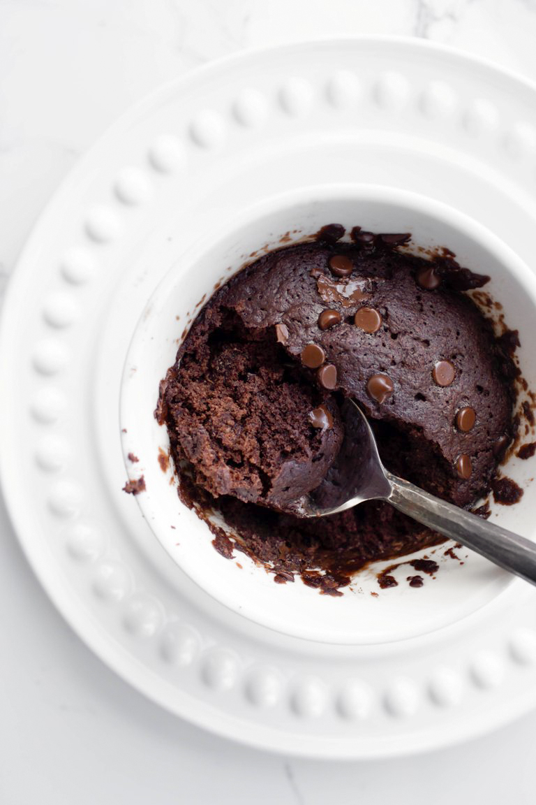 Cooked vegan chocolate mug cake with spoon inside