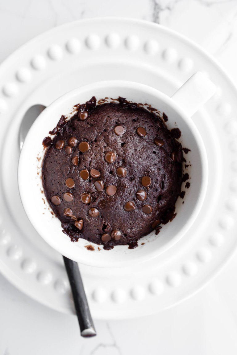 Cooked vegan chocolate mug cake in white mug on white plate