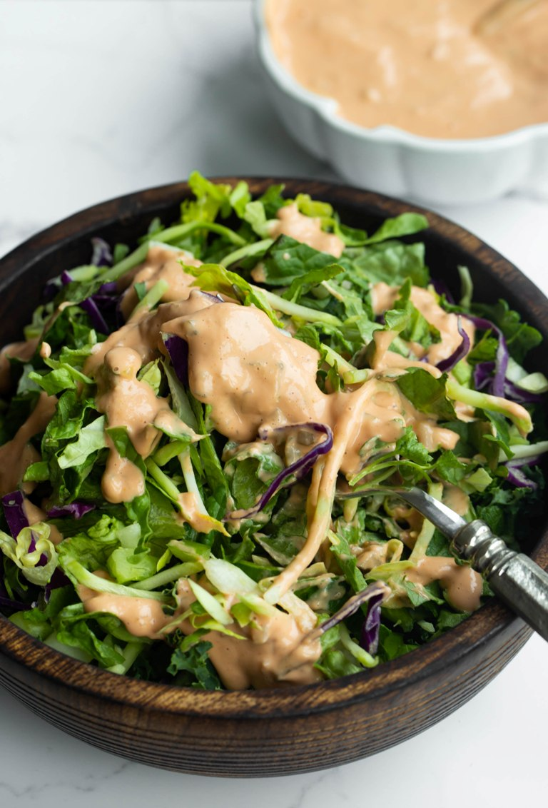 fork sticking in salad with vegan thousand island dressing drizzled on top