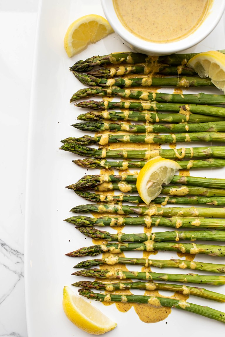 spread out baked asparagus with lemon sauce drizzled on top