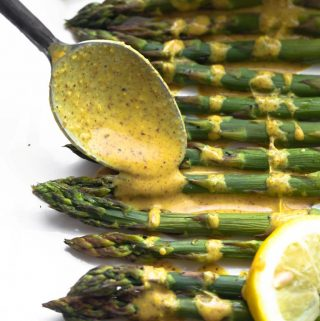 Spoon drizzling lemon ginger sauce on top of baked asparagus