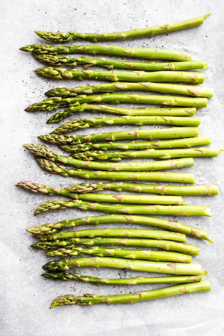 spread out asparagus spears on baking sheet
