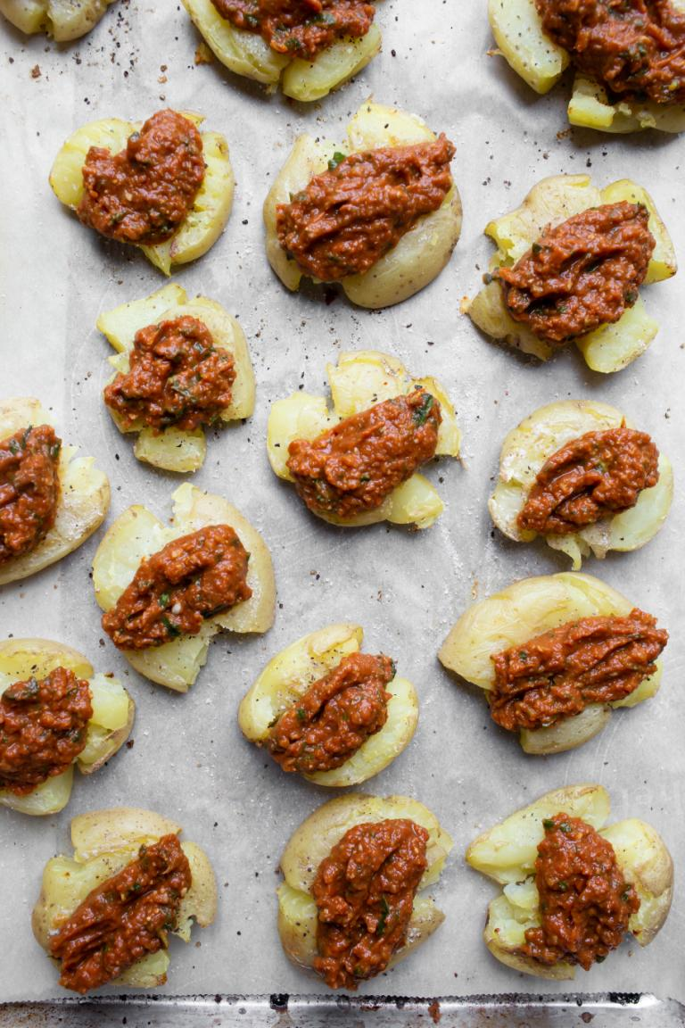 smashed potatoes with sun-dried tomato pesto dollop on top each one