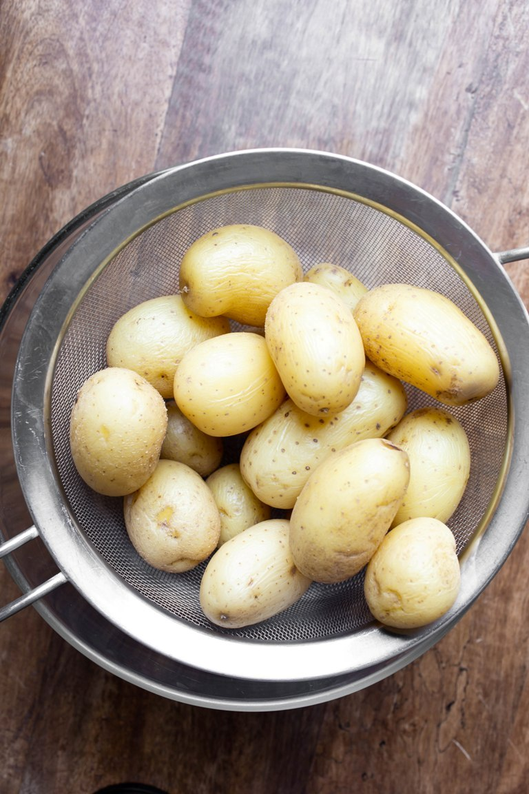 gold potatoes being strained into a bowl
