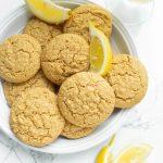 gorgeous bright shot of several lemon cookies with fresh lemon