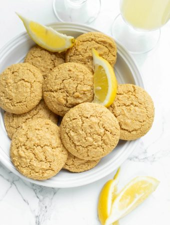 gorgeous bright shot of several lemon cookies with fresh lemon