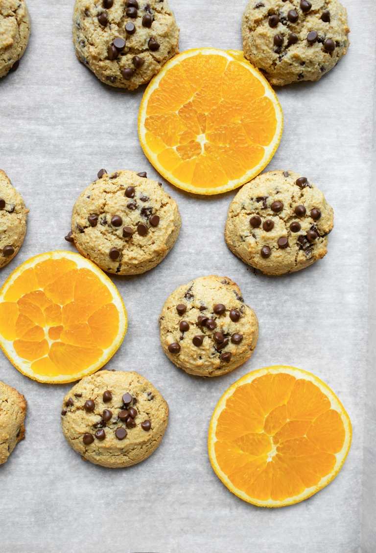 baked orange chocolate chip cookies on pan with orange slices