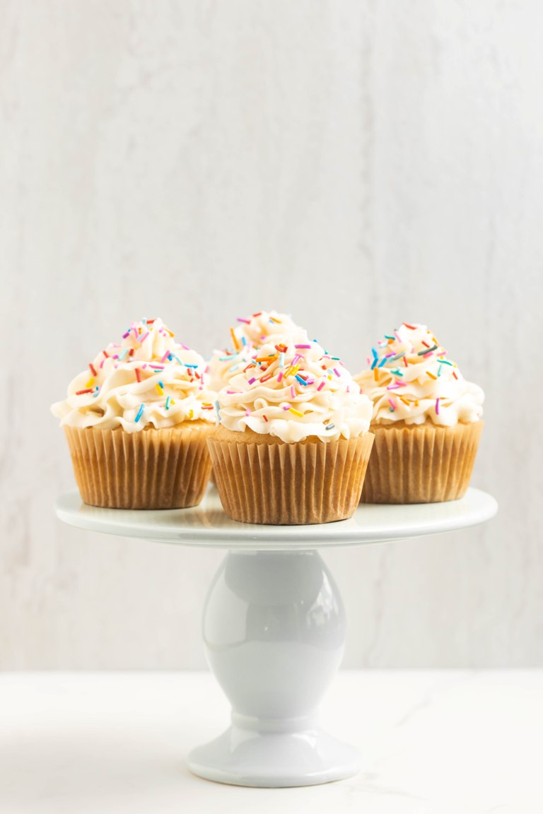 cake stand with vanilla cupcakes on top