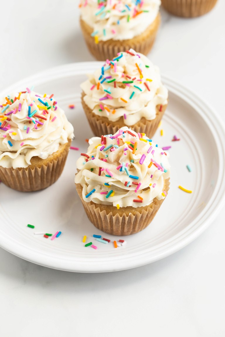 3 cupcakes with buttercream on a white plate