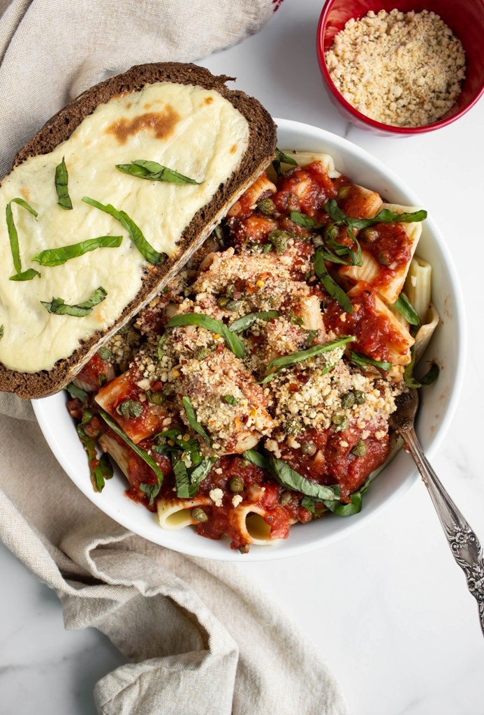 bowl of pasta with fresh basil and toast with melted vegan cheese