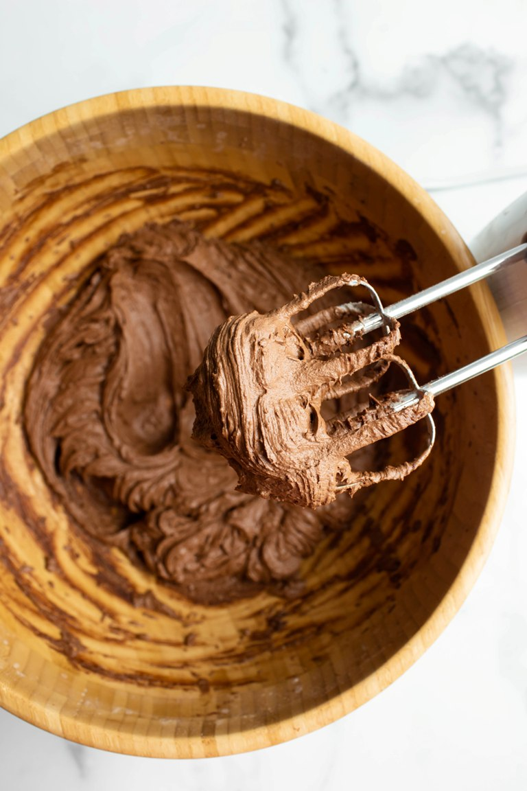 beaters showing chocolate frosting above wooden bowl