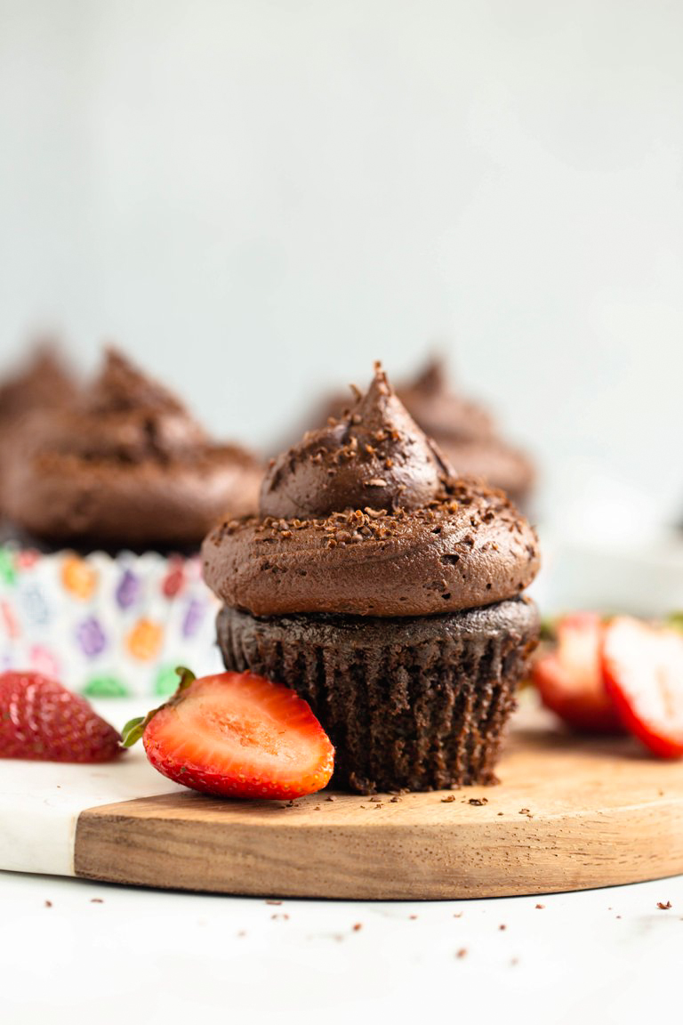 chocolate cupcake with frosting on board with strawberries