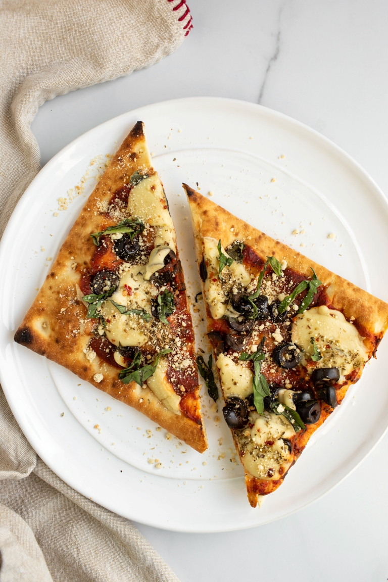vegan pizza with vegan parmesan cheese and toppings