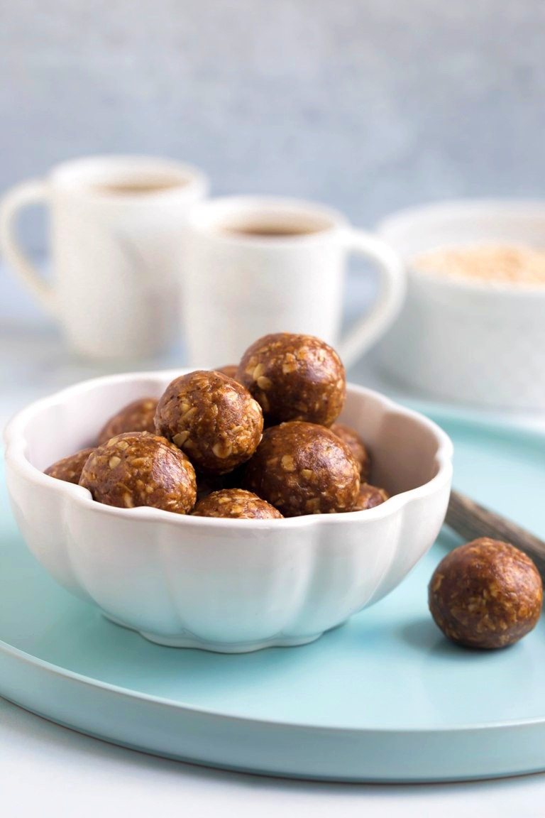 white bowl of chai balls with 2 cups of coffee