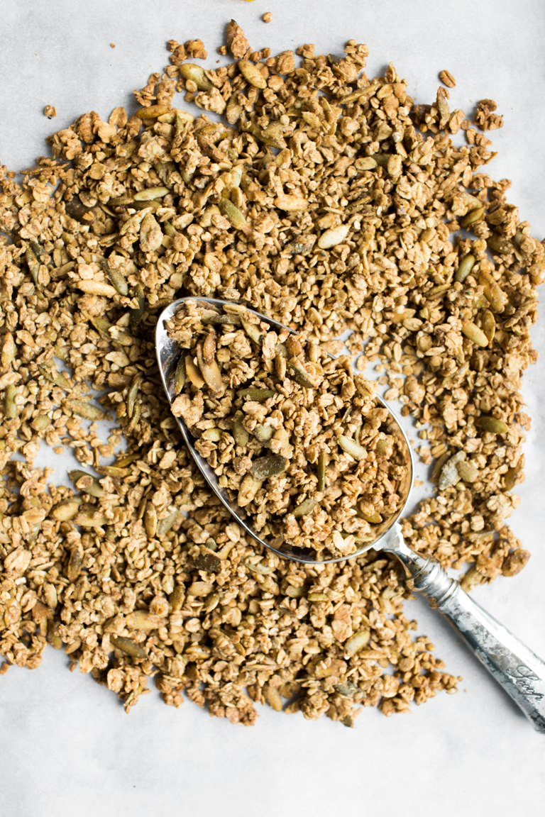 baked spiced buckwheat granola on pan with spoon in middle