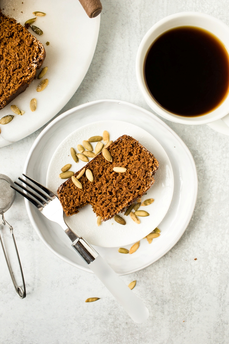 slice of vegan pumpkin bread on white plate with coffee