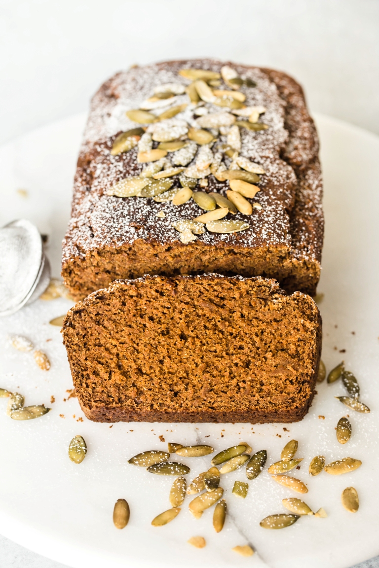 sliced vegan pumpkin bread with powdered sugar