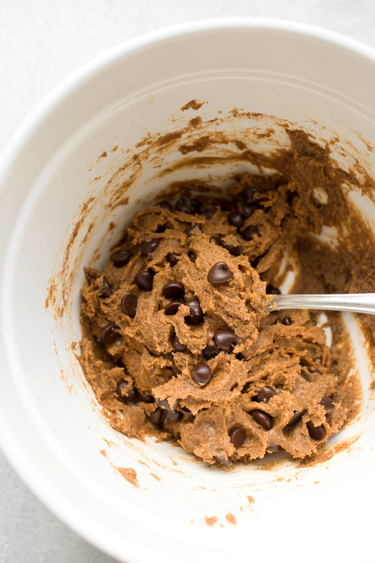 vegan pumpkin chocolate chip cookie batter in white bowl