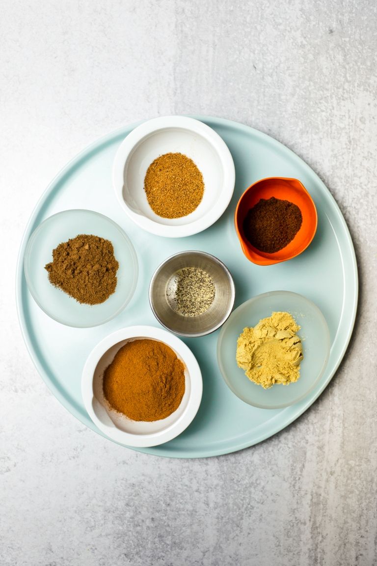 pumpkin pie spices in bowls on blue plate