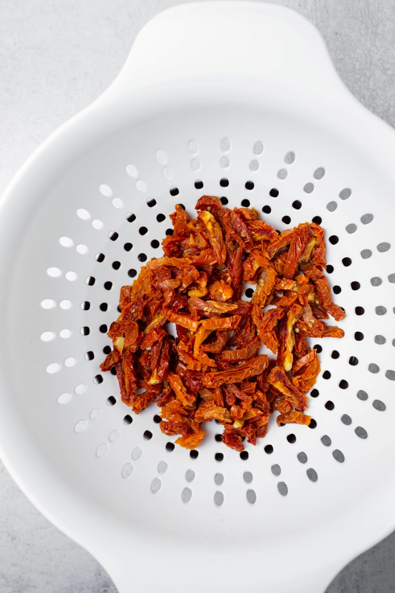 white colander of soaked sun-dried tomatoes