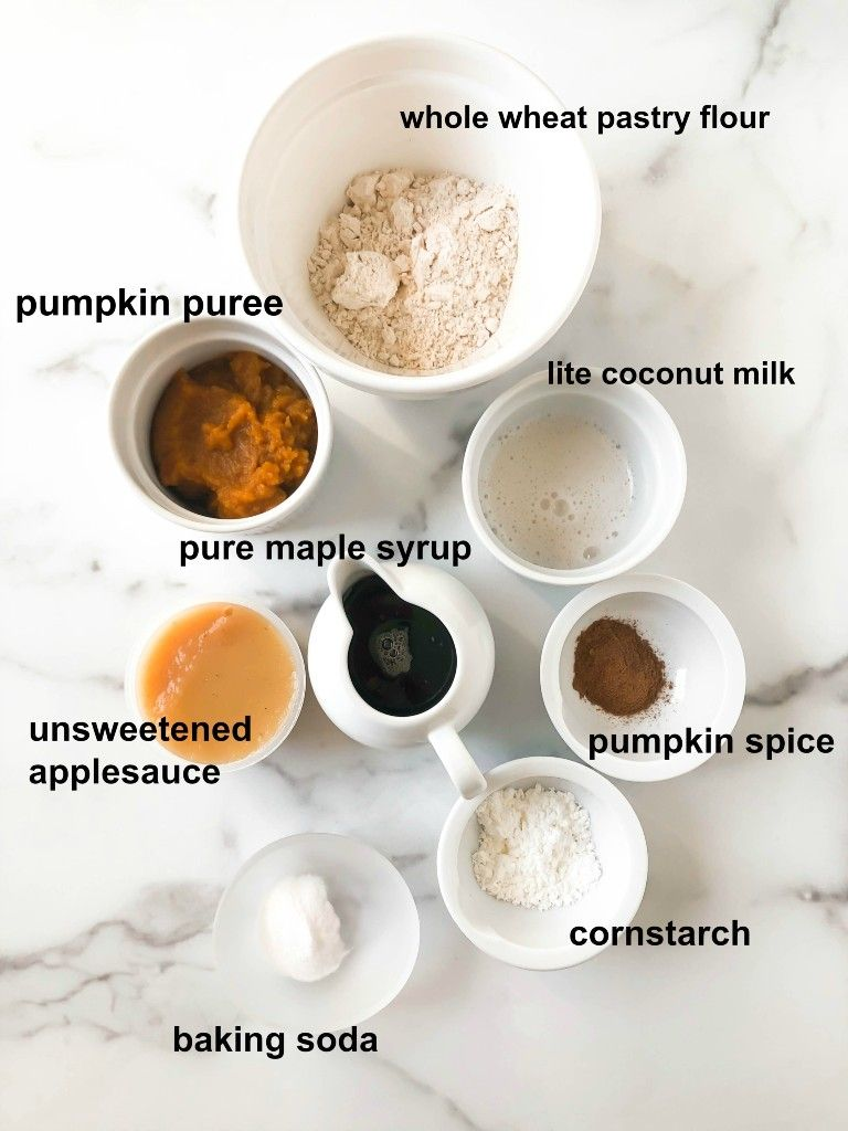 ingredients for vegan pumpkin cake in separate bowls on white marble