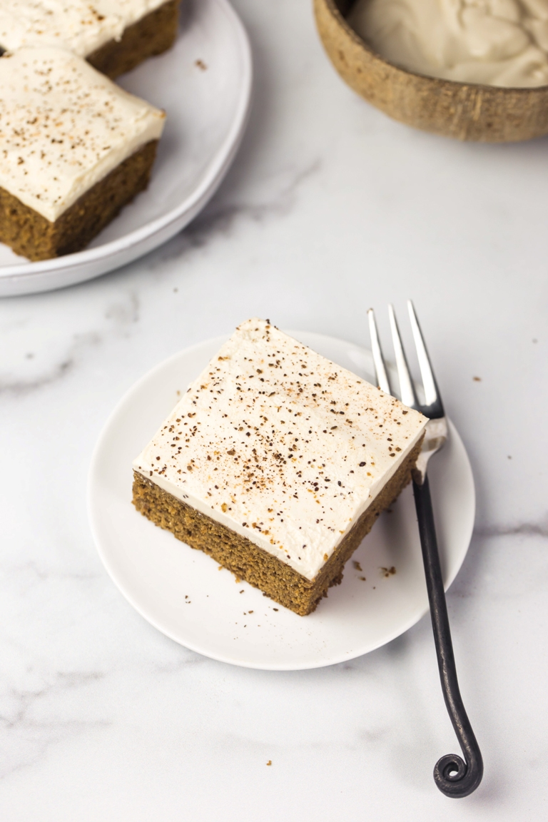 slice of vegan pumpkin cake with frosting on white plate