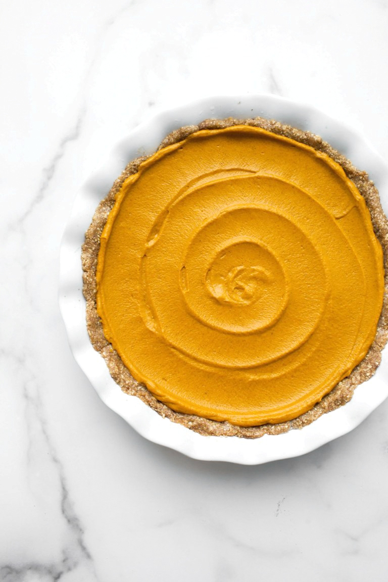 Vegan pumpkin pie batter smoothed out into pie crust